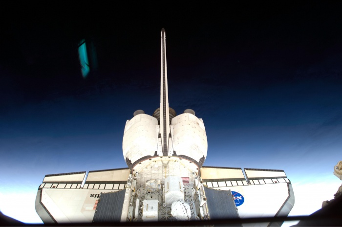 On flight day four of the STS-129 mission, a member of the crew photographed the aft section of space shuttle Atlantis through a window from aboard the International Space Station. Reflections on the window are visible in this image. The 11-day shuttle mission continued maintenance and upgrades to the orbital outpost. Date: 25 November 2009  Source: NASA Image of the Day