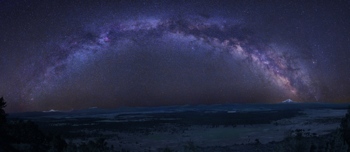 A Graceful Arc: Milky Way Astronomy Picture of the Day - 2009 December 25 Credit & Copyright: Tony Hallas  Explanation: The graceful arc of the Milky Way begins and ends at two mountain peaks in this solemn night sky panorama. Created from a 24 frame mosaic, exposures tracking Earth and sky were made separately, with northern California's Mount Lassen at the left and Mount Shasta at the far right, just below the star and dust clouds of the galactic center. Lassen and Shasta are volcanoes in the Cascade Mountain Range of North America, an arc of the volcanic Pacific Ring of Fire. In the dim, snow-capped peaks, planet Earth seems to echo the subtle glow of the Milky Way's own faint, unresolved starlight.