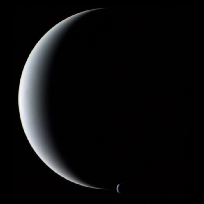Crescent Neptune and Triton Astronomy Picture of the Day - 2009 December 13 Credit: Voyager 2, NASA  Explanation: Gliding silently through the outer Solar System, the Voyager 2 spacecraft camera captured Neptune and Triton together in crescent phase in 1989. The above picture of the gas giant planet and its cloudy moon was taken from behind just after closest approach. It could not have been taken from Earth because Neptune never shows a crescent phase to sunward Earth. The unusual vantage point also robs Neptune of its familiar blue hue, as sunlight seen from here is scattered forward, and so is reddened like the setting Sun. Neptune is smaller but more massive than Uranus, has several dark rings, and emits more light than it receives from the Sun.