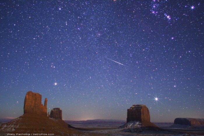 Geminid Meteor over Monument Valley Astronomy Picture of the Day - 2009 December 12 Credit & Copyright: Wally Pacholka (AstroPics.com, TWAN)  Explanation: The Geminids are expected to put on a good show this year. Created as planet Earth sweeps through dusty debris from extinct comet Phaethon, the annual Geminid meteor shower is predicted to peak on December 14th, around 0510 UT (12:10am EST). With better viewing for northern hemisphere observers, pictures of Geminids streaking through the night could include wintery landscapes, like this snow-tinged image of a 2007 Geminid meteor over buttes of the Monument Valley region in the southwestern US. The meteor streak points back to the constellation Gemini and the shower's radiant point, just off the upper left edge of the scene. Along with Rigel, the sword and belt stars of Orion are at the upper right. Near the eastern horizon are bright stars Procyon (left) and Sirius. The two buttes at the far left are known as The Mittens - clearly a reminder that if you want to watch a meteor shower on a cold December night, wearing mittens would be a good idea.