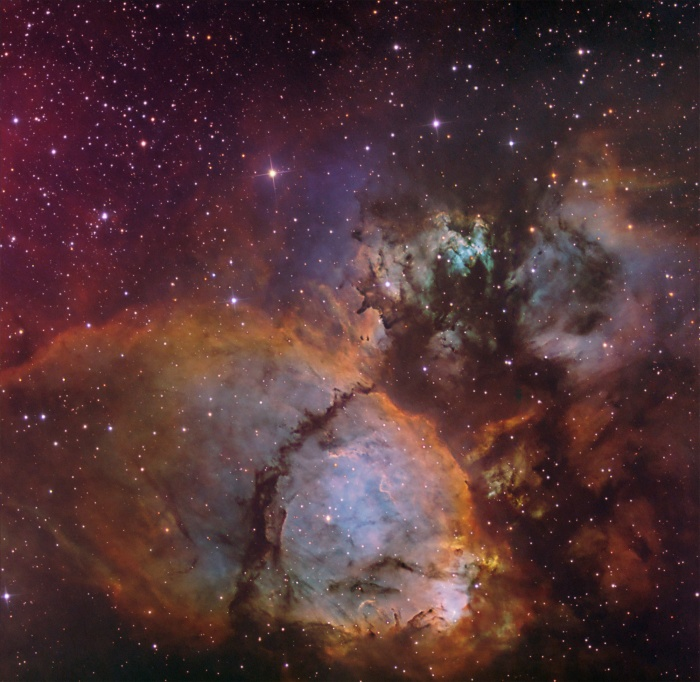 The Colors of IC 1795 Astronomy Picture of the Day - 2009 December 10 Credit & Copyright: Don Goldman  Explanation: This colorful cosmic portrait features glowing gas and obscuring dust clouds in IC 1795, a star forming region in the northern constellation Cassiopeia. The nebula's colors were created by adopting the Hubble false-color palette for mapping narrow emission from oxygen, hydrogen, and sulfur atoms to blue, green and red colors, and further blending the data with images of the region recorded through broadband filters. Not far on the sky from the famous Double Star Cluster in Perseus, IC 1795 is itself located next to IC 1805, the Heart Nebula, as part of a complex of star forming regions that lie at the edge of a large molecular cloud. Located just over 6,000 light-years away, the larger star forming complex sprawls along the Perseus spiral arm of our Milky Way Galaxy. At that distance, this picture would span about 70 light-years across IC 1795.