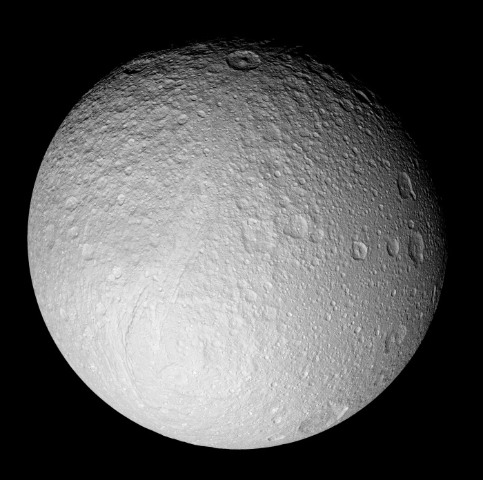Ice Moon Tethys from Saturn-Orbiting Cassini Astronomy Picture of the Day - 2009 December 8 Credit: Cassini Imaging Team, SSI, JPL, ESA, NASA  Explanation: What processes formed the unusual surface of Saturn's moon Tethys? To help find out, NASA sent the robotic Cassini spacecraft right past the enigmatic ice moon in 2005. Pictured above is one of the highest resolution images of an entire face of Tethys yet created. The pervasive white color of Tethys is thought to be created by fresh ice particles continually falling onto the moon from Saturn's diffuse E-ring -- particles expelled by Saturn's moon Enceladus. Some of the unusual cratering patterns on Tethys remain less well understood, however. Close inspection of the above image of Tethys' south pole will reveal a great rift running diagonally down from the middle: Ithaca Chasma. A leading theory for the creation of this great canyon is anchored in the tremendous moon-wide surface cracking that likely occurred when Tethys' internal oceans froze. If so, Tethys may once have harbored internal oceans, possibly similar to the underground oceans some hypothesize to exist under the surface of Enceladus today. Might ancient life be frozen down there?