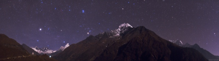 Himalayan Skyscape Astronomy Picture of the Day - 2009 December 5 Credit & Copyright: Babak Tafreshi (TWAN)  Explanation: Capella, alpha star of the constellation Auriga, rises over Mt. Everest in this panoramic view of the top of the world at night. The scene was recorded in late November near Namche Bazar, Nepal, gateway to the Himalayan mountain range. Moonlight illuminates the famous peaks of Everest (8840 meters) and Lhotse (8516 meters) at the far left, and a stupa (a Buddhist religious monument) in the foreground, along the main trail to the Everest Base Camp. The light in the valley is from the Tengboche Monastery, also along the trail at about 4000 meters. From left to right above the moonlit peaks, the stars of Auriga give way to bright giant star Aldebaran eye of the Taurus the Bull, the Pleiades star cluster, alpha Ceti, and finally alpha Phoenicis of the Phoenix. Peaks and stars can be identified by placing your cursor over the image.