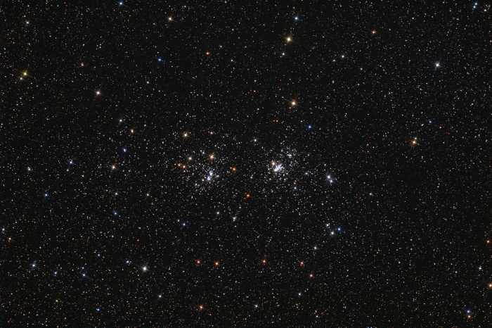 The Double Cluster Astronomy Picture of the Day - 2009 December 4 Credit & Copyright: Neil Fleming  Explanation: A lovely starfield in the heroic northern constellation Perseus holds this famous pair of open or galactic star clusters, h and Chi Perseii. Also cataloged as NGC 869 (right) and NGC 884, both clusters are about 7,000 light-years away and contain stars much younger and hotter than the Sun. Separated by only a few hundred light-years, the clusters' ages based on their individual stars are similar - evidence that they were likely a product of the same star-forming region. Always a rewarding sight in binoculars, the Double Cluster is even visible to the unaided eye from dark locations. Star colors (and spikes) are enhanced in this beautiful, wide field, telescopic image.