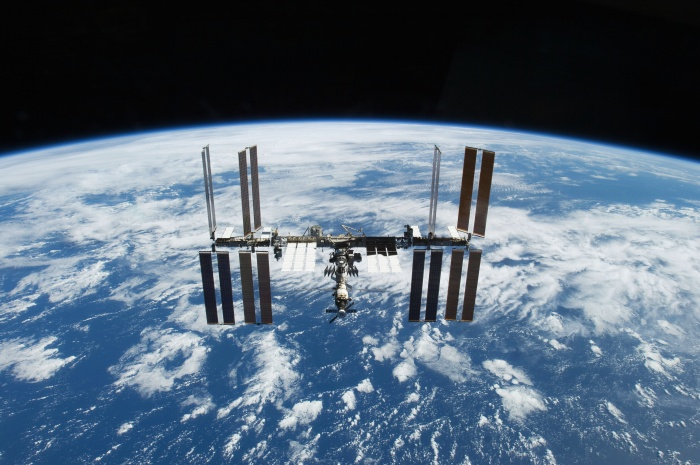 The International Space Station orbits over a blue-and-white Earth, backdropped by the blackness of Space, November 25, 2009.  Credit: NASA