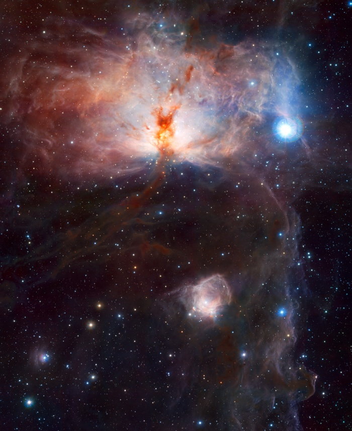 The Flame Nebula in Infrared Credit & Copyright: ESO/J. Emerson/VISTA; Acknowledgment: Cambridge Astronomical Survey Unit Astronomy Picture of the Day - 2010 January 12  Explanation: What lights up the Flame Nebula? Fifteen hundred light years away towards the constellation of Orion lies a nebula which, from its glow and dark dust lanes, appears, on the left, like a billowing fire. But fire, the rapid acquisition of oxygen, is not what makes this Flame glow. Rather the bright star Alnitak, the easternmost star in the Belt of Orion visible just above the nebula, shines energetic light into the Flame that knocks electrons away from the great clouds of hydrogen gas that reside there. Much of the glow results when the electrons and ionized hydrogen recombine. The above false-color picture of the Flame Nebula (NGC 2024) was taken in infrared light, where a young star cluster becomes visible. The Flame Nebula is part of the Orion Molecular Cloud Complex, a star-forming region that includes the famous Horsehead Nebula, visible above on the far right.