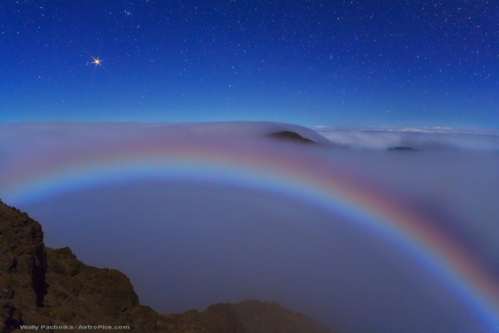 Mars and a Colorful Lunar Fog Bow Credit & Copyright: Wally Pacholka (AstroPics.com, TWAN) Astronomy Picture of the Day - 2010 February 2  Explanation: Even from the top of a volcanic crater, this vista was unusual. For one reason, Mars was dazzlingly bright two weeks ago, when this picture was taken, as it was nearing its brightest time of the entire year. Mars, on the far upper left, is the brightest object in the above picture. The brightness of the red planet peaked last week near when Mars reached opposition, the time when Earth and Mars are closest together in their orbits. Arching across the lower part of the image is a rare lunar fog bow. Unlike a more commonly seen rainbow, which is created by sunlight reflected prismatically by falling rain, this fog bow was created by moonlight reflected by the small water drops that compose fog. Although most fog bows appear white, all of the colors of the rainbow were somehow visible here. The above image was taken from high atop Haleakala, a huge volcano in Hawaii, USA.