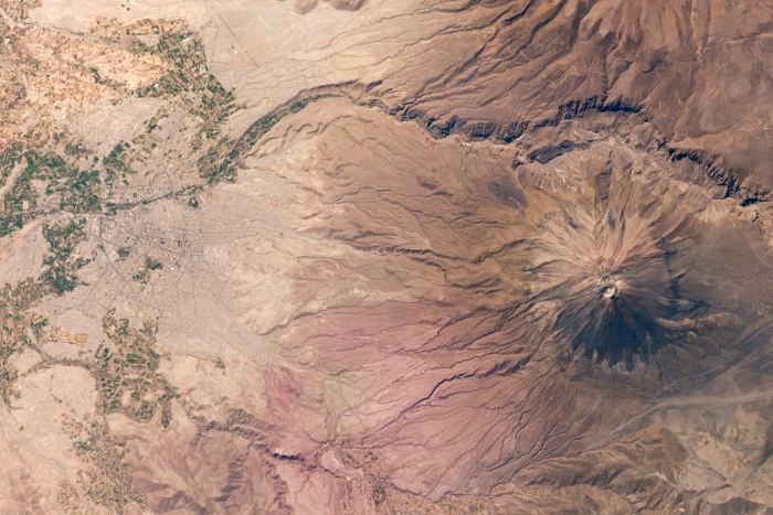 """Several Latin American cities have grown up on the flanks of active volcanoes. This mosaic of two astronaut photographs illustrates the closeness of Arequipa, Peru, to the 5,822-meter- (19,100-foot-) high El Misti Volcano. The symmetric conical shape of El Misti is typical of a stratovolcano, a type of volcano characterized by alternating layers of lava and debris from explosive eruptions, such as ash and pyroclastic flows. Stratovolcanoes are usually located on the continental crust above a subducting tectonic plate. The magma feeding the stratovolcanoes of the Andes Mountains, including El Misti, is associated with ongoing subduction of the Nazca Plate beneath the South American Plate. El Misti's most recent—and relatively minor—eruption occurred in 1985.  The city center of Arequipa, Peru, lies only 17 kilometers (11 miles) away from the summit of El Misti; the gray urban area is bordered by green agricultural fields (image left). With almost 1 million residents in 2009, it is the second largest city in Peru in terms of population. Much of the building stone for Arequipa, known locally as sillar, is quarried from nearby pyroclastic flow deposits that are white. Arequipa is known as the """"White City"""" because of the prevalence of this building material. The Chili River extends northeastwards from the city center and flows through a canyon (image right) between El Misti volcano and Nevado Chachani to the north. Nevado Chachani is a volcanic complex that may have erupted during the Holocene Epoch (from about 10,000 years ago to the present), but no historical eruptions have been observed there.  Astronaut photographs ISS021-E-8370 and ISS021-E-8371 were was acquired on October 16, 2009, with a Nikon D2Xs camera fitted with a 180 mm lens, and are provided by the ISS Crew Earth Observations experiment and Image Science & Analysis Laboratory, Johnson Space Center. The image was taken by the Expedition 21 crew. The image in this article has been cropped and enhanced to im"""