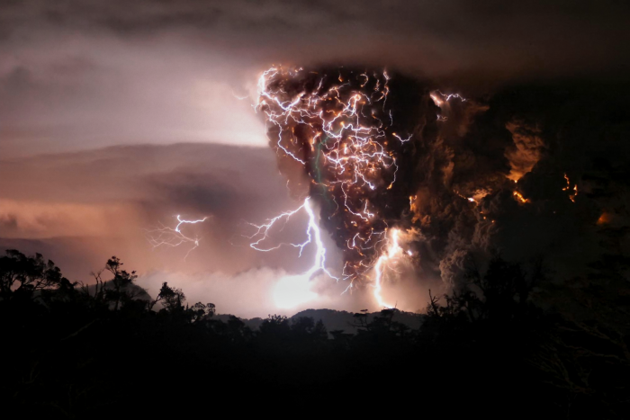 Lightning bolts appear above and around the Chaitén volcano in southern Chile as seen from Chana, some 30 kilometers north of the volcano. The mingling of lightning and ash is a so called dirty thunderstorm. These storms may be sparked when rock fragments, ash, and ice particles in the plume collide to produce static charges, just as ice particles collide to create charge in regular thunderstorms.  Image Credit: Carlos Gutierrez/UPI/astroarts.org