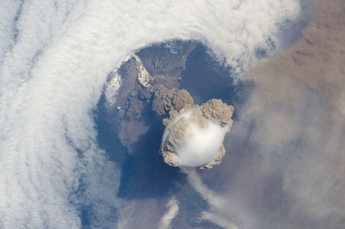International Space Station Imagery: Sarychev Peak Volcano eruption, Kuril Islands ISS020-E-009048 (12 June 2009) --- Sarychev Peak Volcano eruption, Kuril Islands, is featured in this image photographed by an Expedition 20 crew member on the International Space Station. A fortuitous orbit of the International Space Station allowed the astronauts this striking view of Sarychev volcano (Russia's Kuril Islands, northeast of Japan) in an early stage of eruption on June 12, 2009. Sarychev Peak is one of the most active volcanoes in the Kuril Island chain and is located on the northwestern end of Matua Island. Prior to June 12, the last explosive eruption had occurred in 1989 with eruptions in 1986, 1976, 1954, and 1946 also producing lava flows. Ash from the June 2009 eruption has been detected 2407 kilometers ESE and 926 kilometers WNW of the volcano, and commercial airline flights are being diverted away from the region to minimize the danger of engine failures from ash intake. This detailed photograph is exciting to volcanologists because it captures several phenomena that occur during the earliest stages of an explosive volcanic eruption. The main column is one of a series of plumes that rose above Matua Island (48.1 degrees north latitude and 153.2 degrees east longitude) on June 12. The plume appears to be a combination of brown ash and white steam. The vigorously rising plume gives the steam a bubble-like appearance; the surrounding atmosphere has been shoved up by the shock wave of the eruption. The smooth white cloud on top may be water condensation that resulted from rapid rising and cooling of the air mass above the ash column, and is probably a transient feature (the eruption plume is starting to punch through). The structure also indicates that little to no shearing winds were present at the time to disrupt the plume. Another series of images, acquired 2-3 days after the start of eruptive activity, illustrate the effect of shearing winds on extent of the as