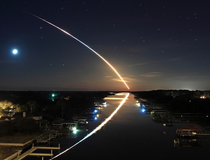 Waterway to Orbit Credit & Copyright: James Vernacotola Astronomy Picture of the Day - 2010 February 13  Explanation: The 32nd shuttle mission to the International Space Station, STS-130, left planet Earth on February 8. Its early morning launch to orbit from Kennedy Space Center's pad 39A followed the long, graceful, eastward arc seen in this 2 minute time exposure. Well composed, the dramatic picture also shows the arc's watery reflection from the Intracoastal Waterway Bridge, in Ponte Vedra, Florida, about 115 miles north of the launch site. In the celestial background a waning crescent Moon and stars left their own short trails against the still dark sky. The brightest star trail near the moon was made by red supergiant Antares, alpha star of the constellation Scorpius.
