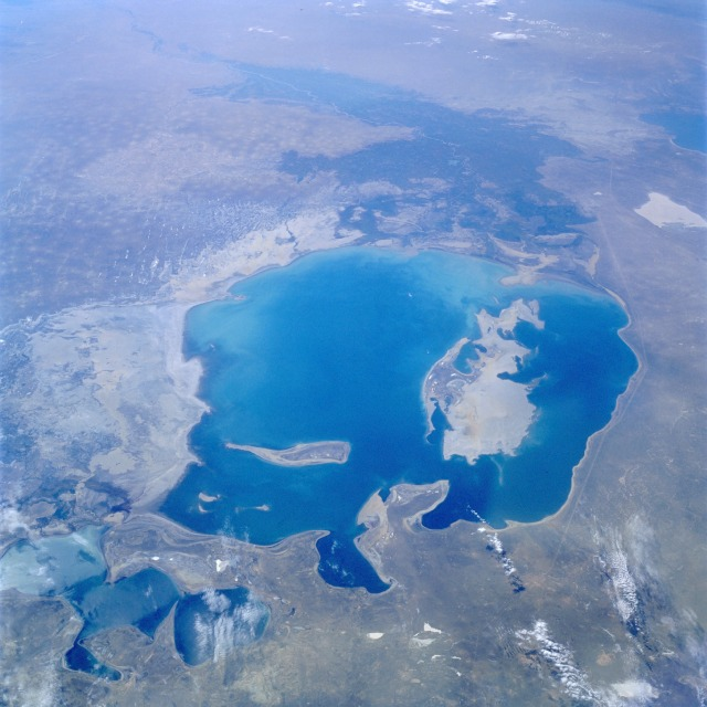 STS047-079-083 Aral Sea, Kazakhstan and Uzbekistan September 1992 A much depleted Aral Sea (refer to the July 1985 photograph STS-51F-036-0059) can be seen in this south-looking, low-oblique view. The emerging, pointed island of Barsa-Kel'mes and the expanding, broad Vozrozhdeniya Island are visible in the center of the sea. Vozrozhdeniya Island is expanding southward toward the Amu Darya River Delta and northward toward the growing Kulandy Peninsula. Continued shrinkage of the Aral Sea water levels will eventually cut off the western portion from the rest of the sea. This phenomenon has already occurred in the extreme northern portion of the sea. Because of dropping water levels, the Karatyup Peninsula (the stretch of land visible north of the main portion of the Aral Sea) has expanded eastward and connected with the delta of the Syr Darya River, cutting off the extreme northern portion from the larger main area of the Aral Sea. With no river inlet into this extreme north portion, it is only a matter of time before this area is reduced to a series of smaller lakes. East of the sea, more exposed shoreline is visible (whitish-gray). It is estimated that the Aral Sea water level has decreased 46 percent since 1960 and is continuing to decrease. The darker areas to the south are the irrigated agricultural lands of the Amu Darya River.
