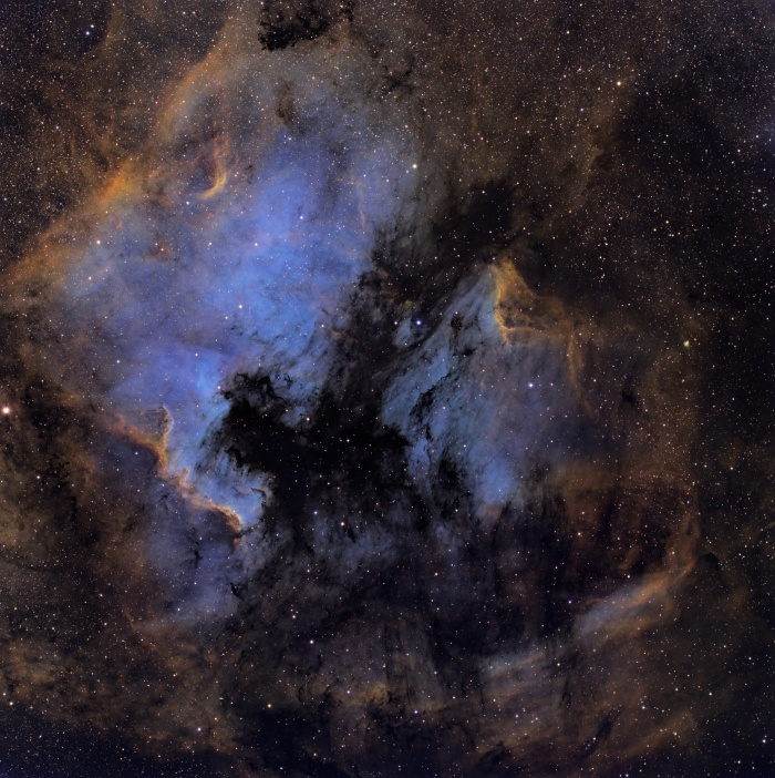 North America and the Pelican   Credit:Martin Pugh Astronomy Picture of the Day -2010 December 18  Explanation: Here lie familiar shapes in unfamiliar locations. On the left is an emission nebula cataloged as NGC 7000, famous partly because it resembles our fair planet's continent of North America. The emission region to the right of the North America Nebula is IC 5070, also known for its suggestive outlines as the Pelican Nebula. Separated by a dark cloud of obscuring dust, the two bright nebulae are about 1,500 light-years away. At that distance, the 4 degree wide field of view spans 100 light-years. This spectacular cosmic portrait combines narrow band images of the region in a false-color palette to highlight bright ionization fronts with fine details of dark, dusty forms in silhouette. Emission from atomic hydrogen, sulfur, and oxygen is captured in the narrow band data. These nebulae can be seen with binoculars from a dark location. Look northeast of bright star Deneb in the constellation Cygnus the Swan.