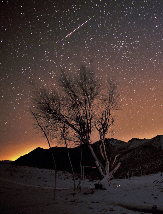 A Meteor Moment  Credit: Amir Hossein Abolfath(TWAN) Astronomy Picture of the Day - 2010 December 17  Explanation: Intensely bright, this fireball meteor flashed through Tuesday's cold, clear, early morning skies over the Karkas Mountains in central Iran, near the peak of the annual Geminid Meteor Shower. To capture the meteor moment and wintery night skyscape, the photographer's camera was fixed to a tripod, its shutter open for about 1.5 minutes. During that time, the multitude of stars slowly traced short, arcing trails through the sky, a reflection of planet Earth's daily rotation on its axis. The meteor's brilliant dash through the scene was brief, though. Changing color as it went, it also left a reddish swirl of hot, glowing gas near the center of its path. The mountains appear in silhouette against the steady glow of distant city lights.