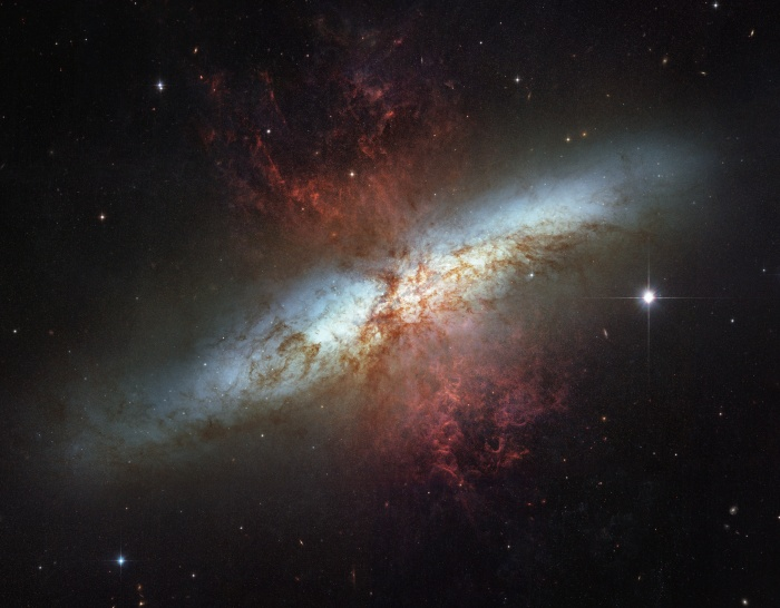 M82: Galaxy with a Supergalactic Wind  Credit:NASA,ESA, TheHubble HeritageTeam, (STScI/AURA) Acknowledgement:M. Mountain(STScI), P. Puxley (NSF),J. Gallagher(U. Wisconsin) Astronomy Picture of the Day -2010 December 19  Explanation: What's lighting up the Cigar Galaxy? M82, as this irregular galaxy is also known, was stirred up by a recent pass near large spiral galaxy M81. This doesn't fully explain the source of the red-glowing outwardly expanding gas, however. Recent evidence indicates that this gas is being driven out by the combined emerging particle winds of many stars, together creating a galactic superwind.. The above photographic mosaic highlights a specific color of red light strongly emitted by ionized hydrogen gas, showing detailed filaments of this gas. The filaments extend for over 10,000 light years. The 12-million light-year distant Cigar Galaxy is the brightest galaxy in the sky in infrared light, and can be seen in visible light with a small telescope towards the constellation of the Great Bear (Ursa Major).