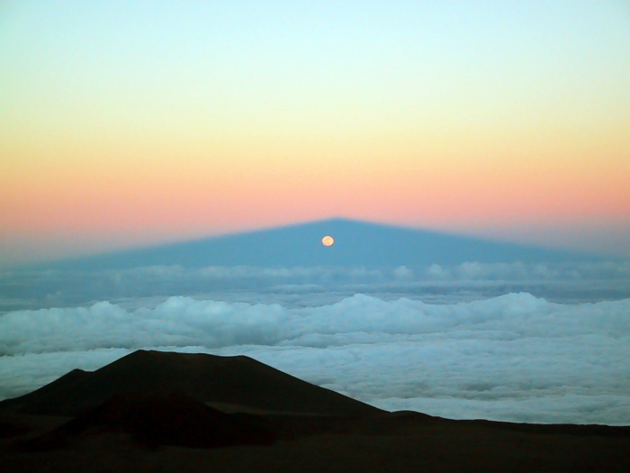 Moonrise Through Mauna Kea's Shadow    Credit:Michael Connelley(U. Hawaii) Astronomy Picture of the Day -2010 December 5  Explanation: How can the Moon rise through a mountain? It cannot -- what was photographed here is a moonrise through the shadow of a large volcano. The volcano is Mauna Kea, Hawai'i, USA, a frequent spot for spectacular photographs since it is arguably the premier observing location on planet Earth. The Sun has just set in the opposite direction, behind the camera. Additionally, the Moon has just passed full phase -- were it precisely at full phase it would rise, possibly eclipsed, at the very peak of the shadow. Refraction of moonlight through the Earth's atmosphere makes the Moon appear slightly oval. Cinder cones from old volcanic eruptions are visible in the foreground. Cloud tops below Mauna Kea's summit have unusually flat tops, indicating a decrease in air moisture that frequently keeps the air unusually dry, anotherattribute of this stellar observing site.