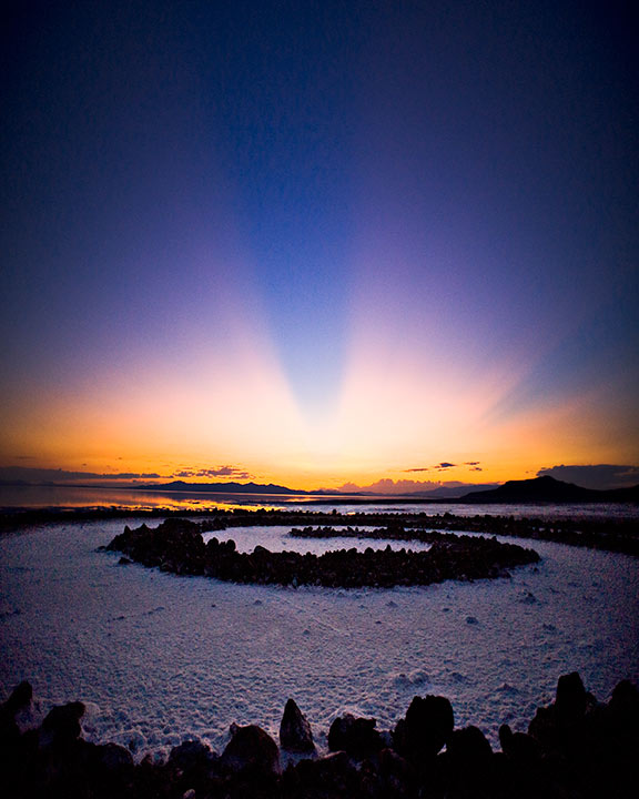 Sunset at the Spiral Jetty  Credit:Arne Erisoty Astronomy Picture of the Day -2010 December 4  Explanation: In dwindling twilight at an August day's end, these broad dark bands appeared in the sky for a moment, seen from Robert Smithson's Spiral Jetty on the eastern shore of Utah's Great Salt Lake. Outlined by rays of sunlight known as crepuscular rays, they are actually shadows cast by clouds near the distant western horizon, the setting Sun having disappeared from direct view behind them. The cloud shadows are parallel, but seem to converge in the distance because of perspective. Coiled in the salt-encrusted lake surface, Smithson's most famous earthwork provides a dramatic contrast to the converging lines. The Spiral Jetty was constructed in 1970, when the water level was unusually low and was completely submerged in a few years as the level rose. Now just above water again, it has spent much of its existence submerged in the briny lake.
