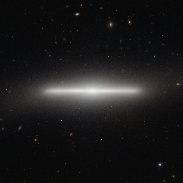 Multiverses: NGC 4452: An Extremely Thin Galaxy  Credit: ESA, Hubble, NAS   Astronomy Picture of the Day - 2010 November 9  Explanation: Why is there a line segment on the sky? In one of the more precise alignments known in the universe, what is pictured above is actually a disk galaxy being seen almost perfectly edge on. The image from the Hubble Space Telescope is a spectacular visual reminder of just how thin disk galaxies can be. NGC 4452, a galaxy in the nearby Virgo Cluster of Galaxies, is so thin that it is actually difficult to determine what type of disk galaxy it is. Its lack of a visible dust lane indicates that it is a low-dust lenticular galaxy, although it is still possible that a view from on top would reveal spiral structure. The unusual stellar line segment spans about 35,000 light years from end to end. Near NGC 4452's center is a slight bulge of stars, while hundreds of background galaxies are visible far in the distance. Galaxies that appear this thin are rare mostly because our Earth must reside (nearly) in the extrapolated planes of their thin galactic disks. Galaxies that actually are this thin are relatively common -- for example our own Milky Way Galaxy is thought to be about this thin.
