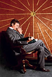 Tesla seated in front of the spiral coil of his high-frequency transformer