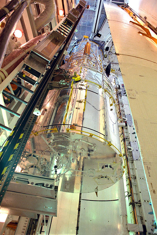 Awaiting deployment, the bus-size Hubble Space Telescope is carefully being transferred from the surgically clean Payload Changeout Room into Discovery's cargo bay at Kennedy Space Center.