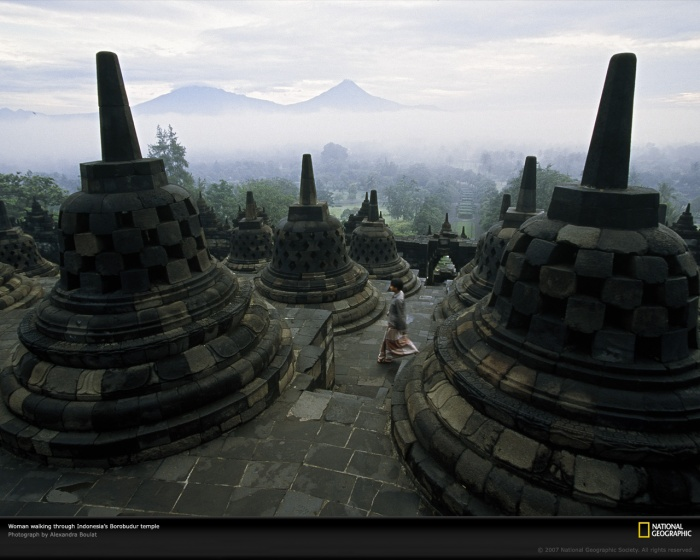 Borobudur Temple, Java, Indonesia, 2001 by National Geographic  A woman walks among the bell-shaped spires of Indonesia's Borobudur—the world's largest Buddhist temple. Built in the jungles of Java during the eighth and ninth centuries A.D., this ancient pilgrimage site lay abandoned for centuries until it was rediscovered and restored in the early 1900s.  (Photo shot on assignment for, but not published in,