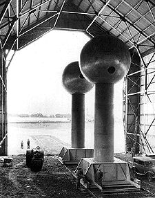 In 1931, when Karl T. Compton became president of Massachusetts Institute of Technology, Van de Graaff was invited to come to MIT as a research associate. In 1931 Van de Graaff constructed his first large machine in an unused aircraft hangar at Round Hill, the estate of Colonel E.H.R. Green, in South Dartmouth, Massachusetts. The machine used two polished aluminum spheres, each 15 feet in diameter mounted on 25 foot high insulating columns, which were 6 feet in diameter. The columns were mounted on railway trucks that boosted the spheres to 43 feet above ground level. The machine had its debut on November 28, 1933 and was able to produce 7,000,000 volts. This accomplishment was reported in the New York Times for November 29, 1933 in a story titled
