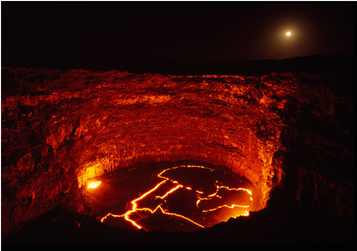 Ethiopia - The infernal glow of a lava lake in the Ertale volcano rivals moonrise over the Danakil Desert. Molten surface temperatures range from 550°F (260° Celsius) near the 262-foot-high (80 meters) walls to nearly 1000°F (538° Celsius) at the center of the pit. (Olivier Grunewald)   Source: National Geographic